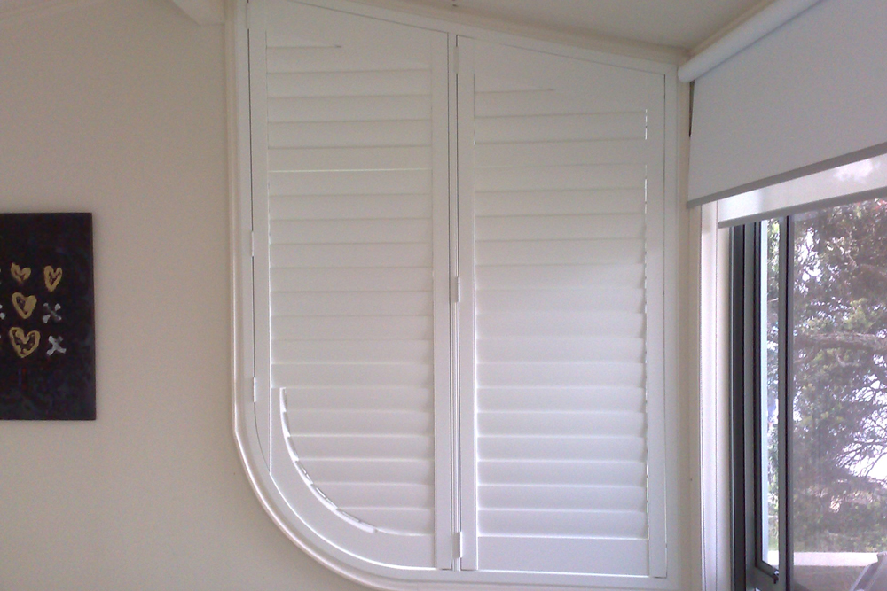 White Santa Fe shaped shutters with curved side