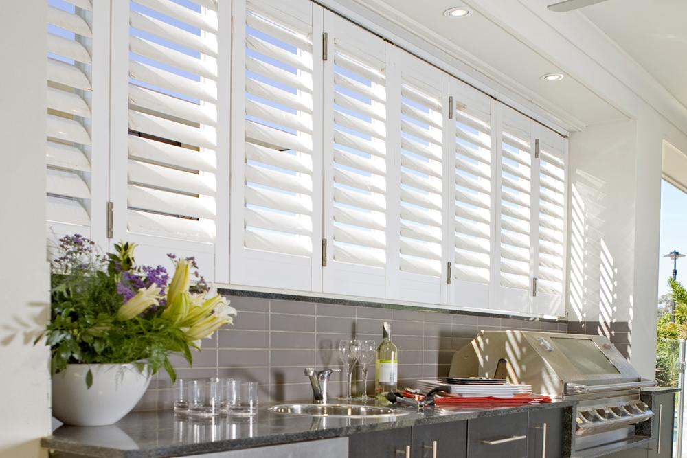 White Santa Fe shutters in outdoor kitchen