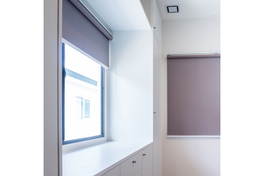 Grey roller blinds for privacy in a bedroom